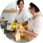 caregiver and old woman washing dishes