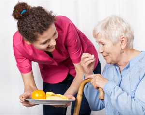 caregiver giving meal to patient