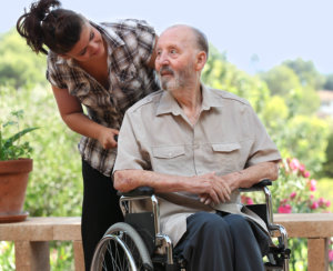 man sitting on a wheelchair with his caregiver